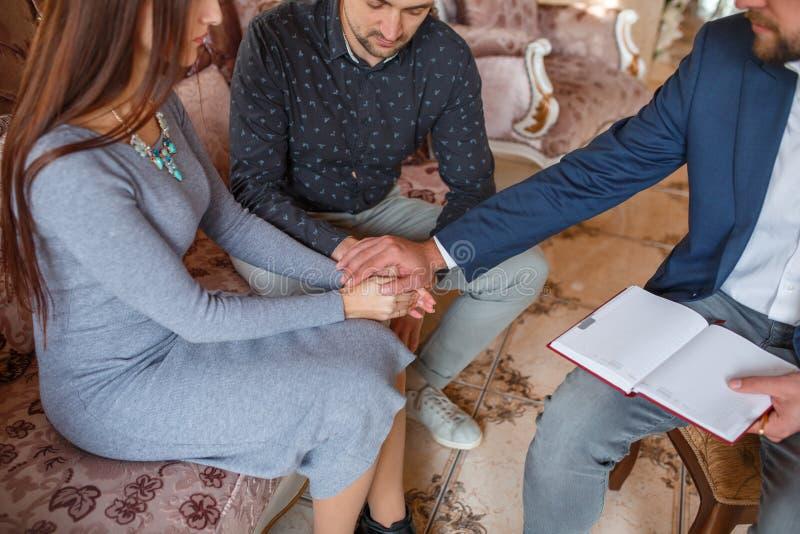 Ett par på ett mottagande på en psykolog rymmer deras händer tillsammans, och doktorn satte hans hand överst arkivbild