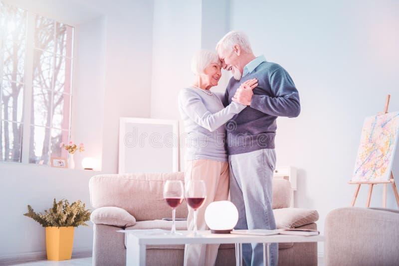 Ett par pensionerade män och kvinnor med extremt romantiskt datum hemma royaltyfri foto