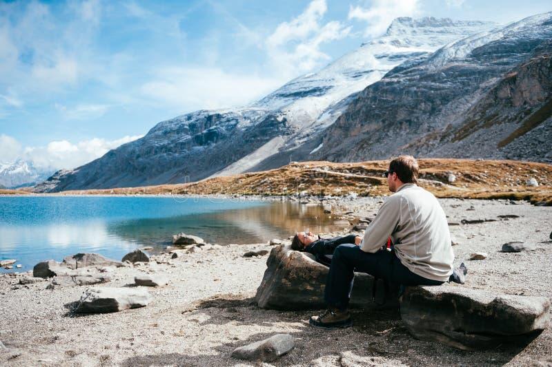 Ett par som framme vilar av en bergig sjö royaltyfri bild