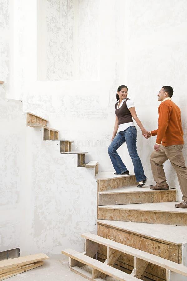 Ett par som går upp trappa royaltyfria bilder