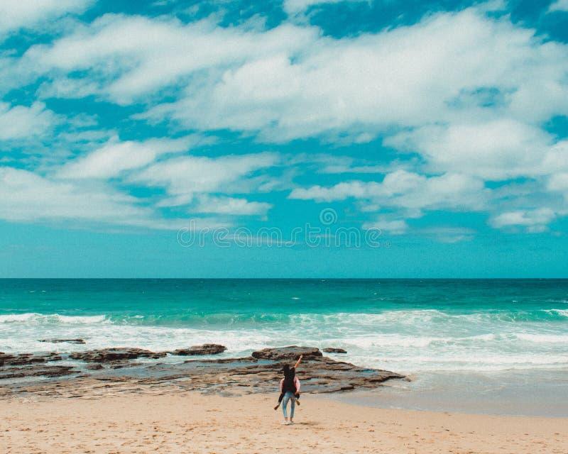 Ett par som har gyckel på den härliga stranden med blå himmel och moln och ett fantastiskt hav arkivfoto
