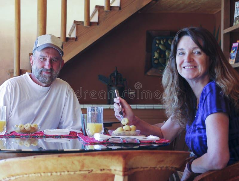 Ett par som har knäpp och orange fruktsaft arkivfoto