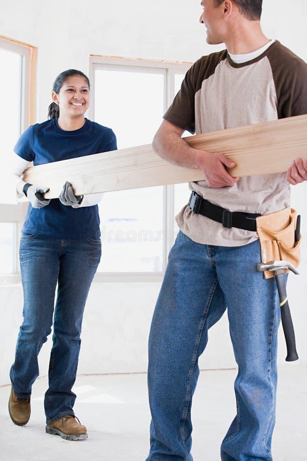 Ett par som rymmer en planka av trä royaltyfri bild