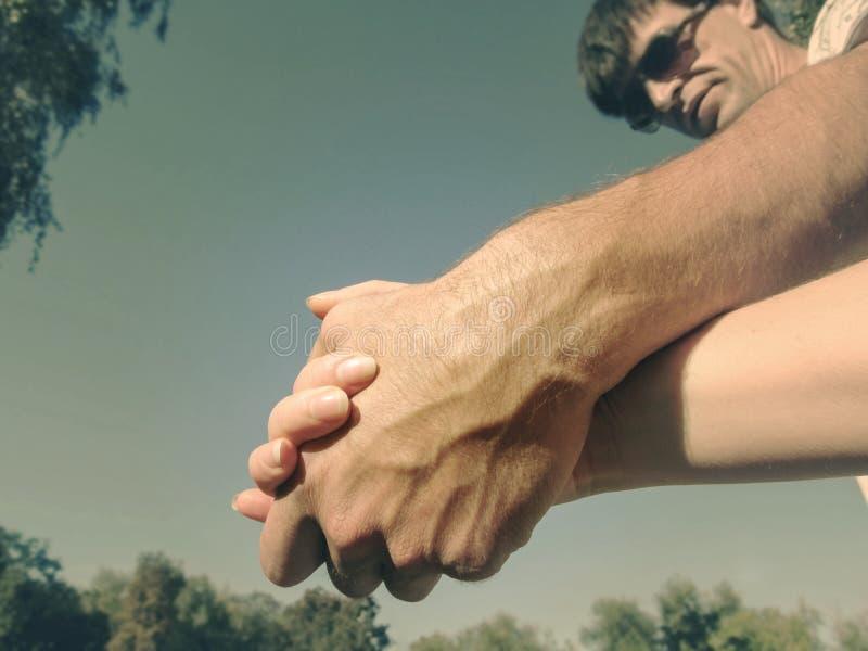 Ett par som rymmer händer mot den blåa himlen, närbild En man i solglasögon rymmer en kvinnas hand, den nedersta sikten, fotousin arkivfoton