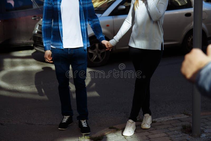 Ett par som rymmer händer och korsar vägen som går runt om staden se vänner arkivfoton