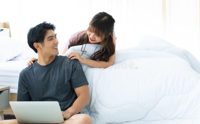 Ett par som söker internet i sovrum royaltyfria foton