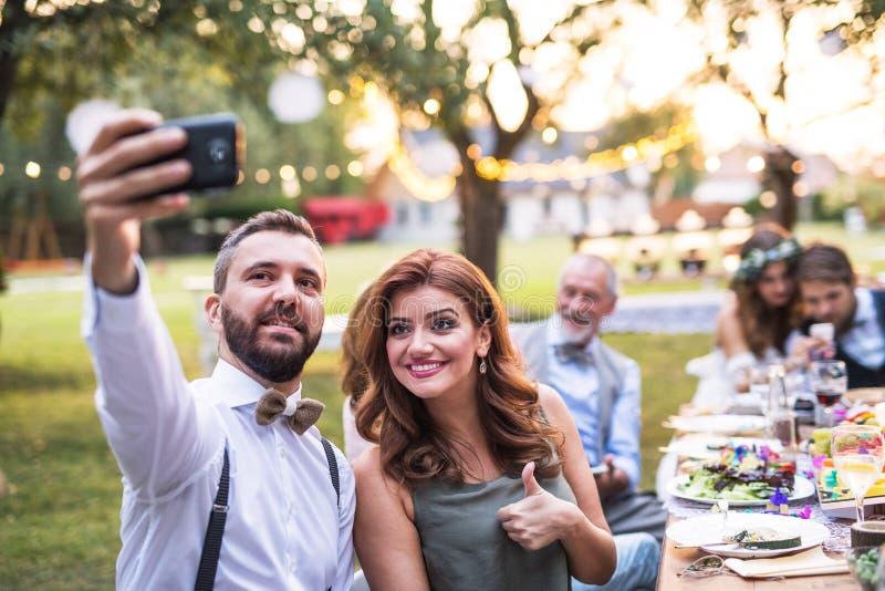 Ett par som tar selfie på bröllopmottagandet utanför i trädgården arkivbild
