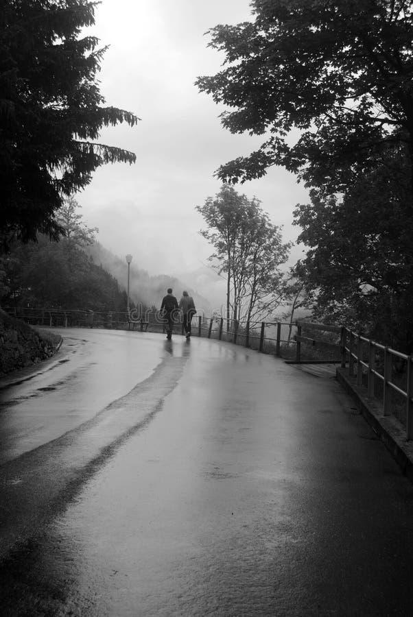 Ett par som tillsammans går ner vägen i en regna dag royaltyfri fotografi