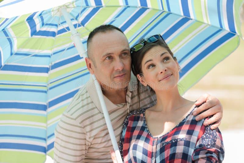 Ett par under parasol fotografering för bildbyråer