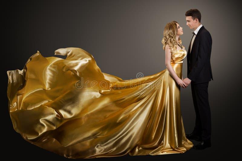 Ett par, vackra kvinnor i Golden Silk Dress och Elegant Man, Fluttering Gown royaltyfri foto