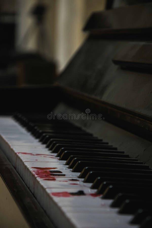 Ett piano med tecken av blod på tangenterna royaltyfri foto