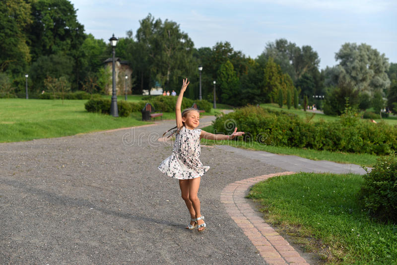 Ett positivt foto av flickadansen på ett passerande i en härlig gräsplan parkerar lite royaltyfri bild