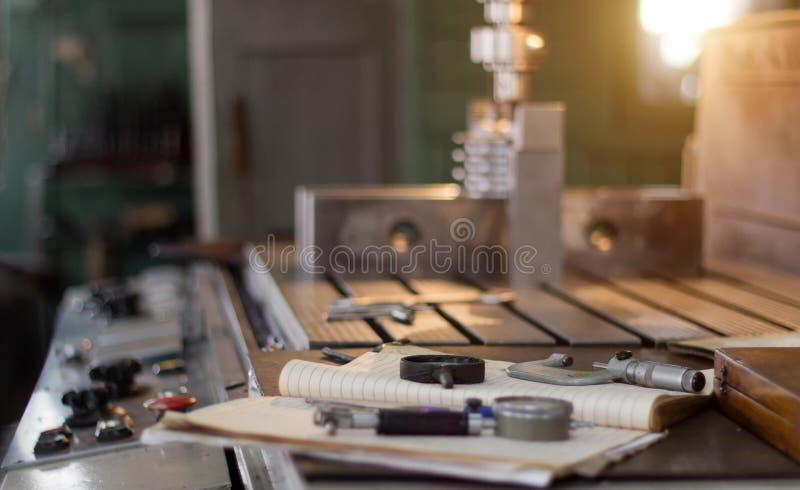 Ett privat seminarium för att arbeta med metalldelar, i bakgrunden en borrandemaskin borrar ett hål i blocket, på arkivbild