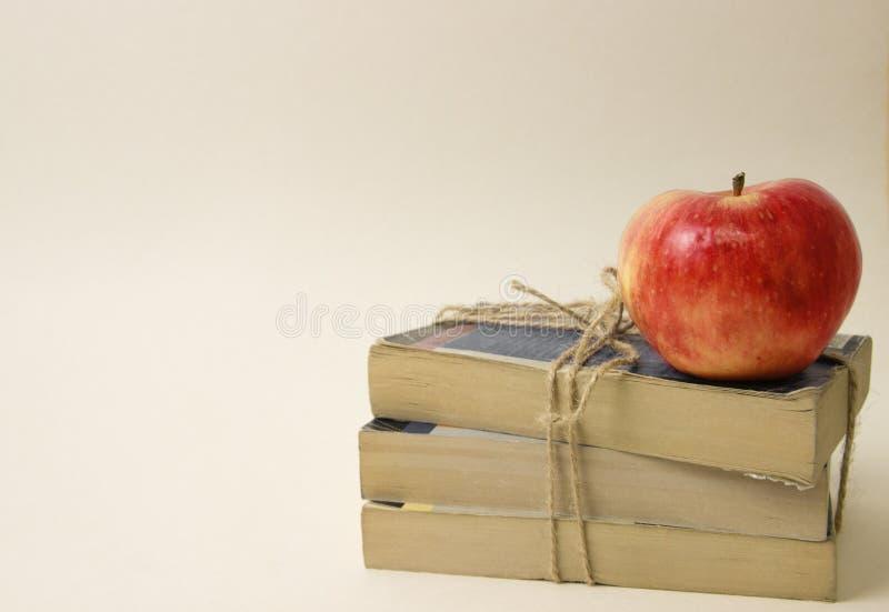 Ett rött äpple ligger på en grupp av böcker, böcker binds med rad arkivbild