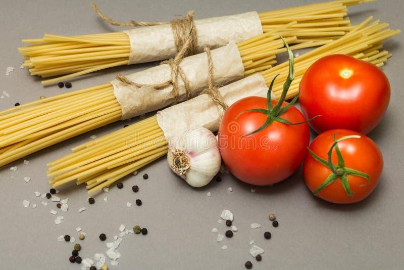 Ett recept för en klassisk pasta på en grå bakgrund Spagetti och grönsaker royaltyfri bild