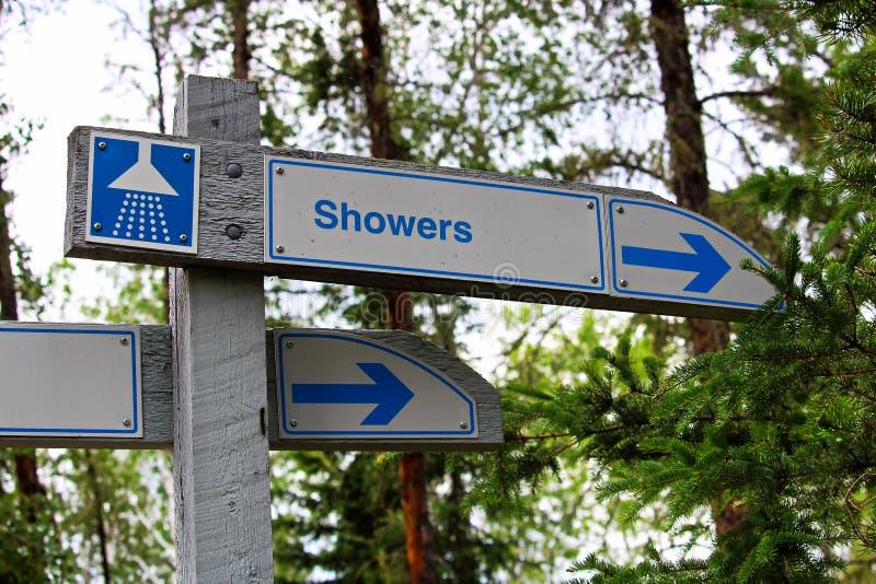 Ett riktningstecken för duschar på en tältplats arkivfoton