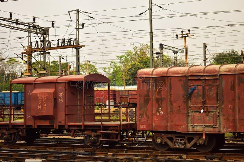 Ett rostigt färgat indiskt godstågvaktrum som binds med godståget arkivbild