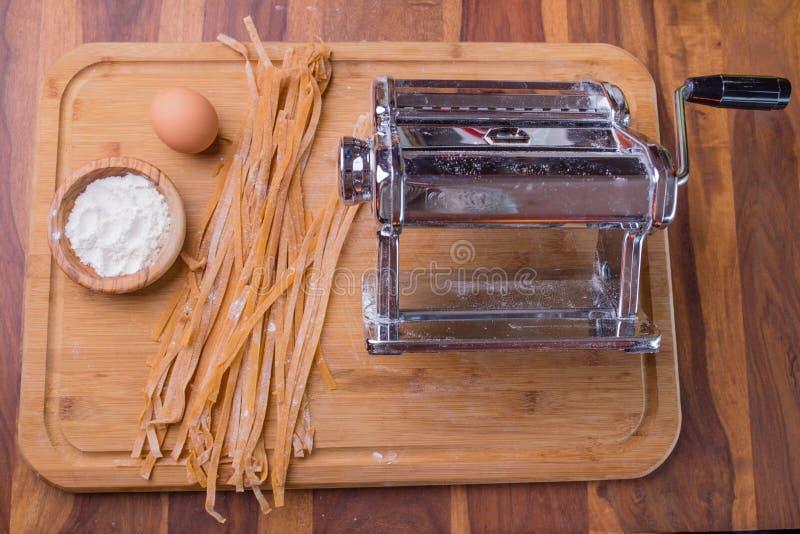 Ett rullande maler med ny pasta, mjöl, ett ägg på en bitande galt royaltyfria bilder