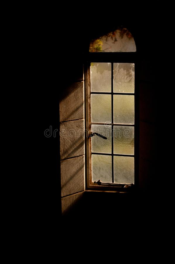 Ett rundat fönster i en svart vägg royaltyfri fotografi