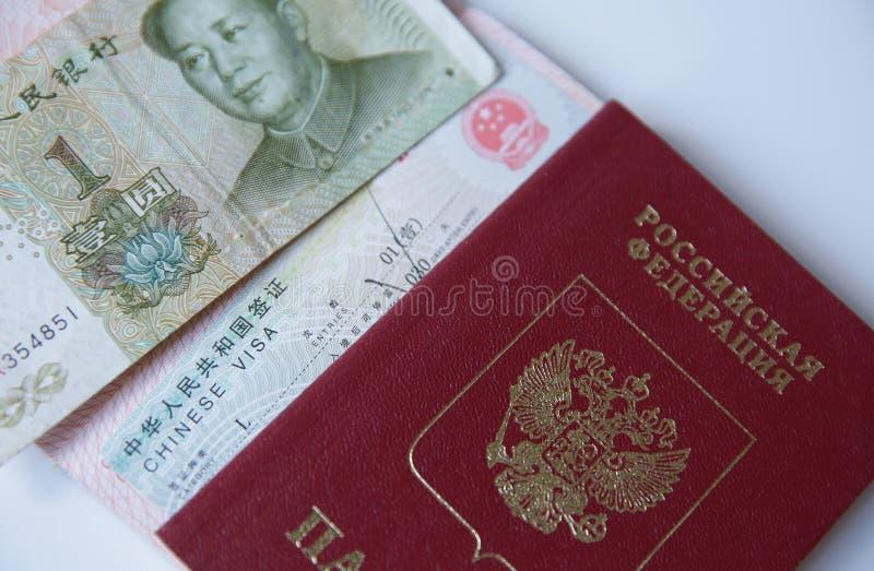 Ett ryskt pass med ett kinesiska visum och pengar är en yuan Visumstämpel, pass f?r dublin f?r bilstadsbegrepp litet lopp ?versik royaltyfri fotografi
