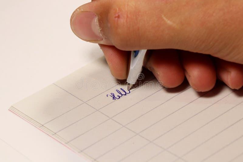 Ett särskilt ord för ung pojkehandstil på papper på diktamen i skola arkivbilder