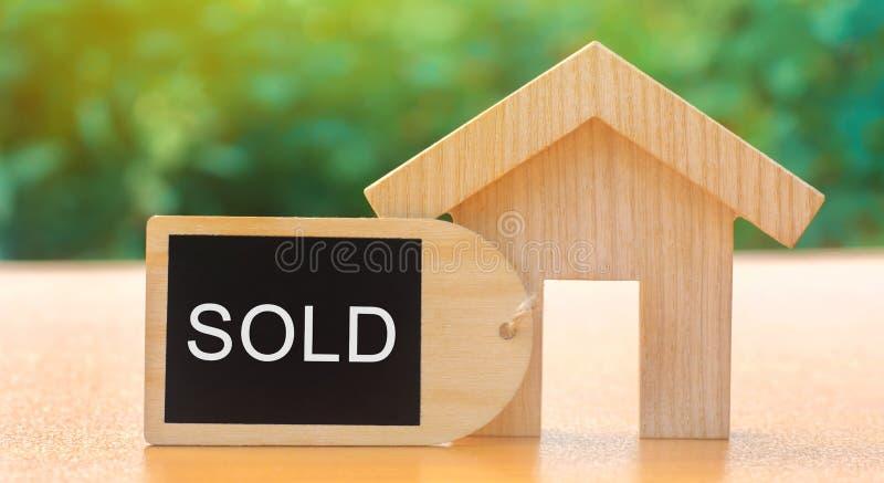 Ett sålda miniatyrträhus och inskrift Begreppet av att sälja ett hem eller en lägenhet Till salu egenskap som man har r?d med hus arkivbilder