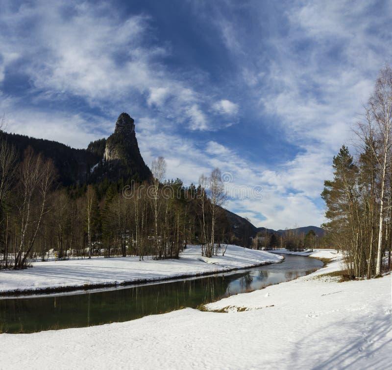 Ett sceniskt berg och en klar flod med snö arkivfoto