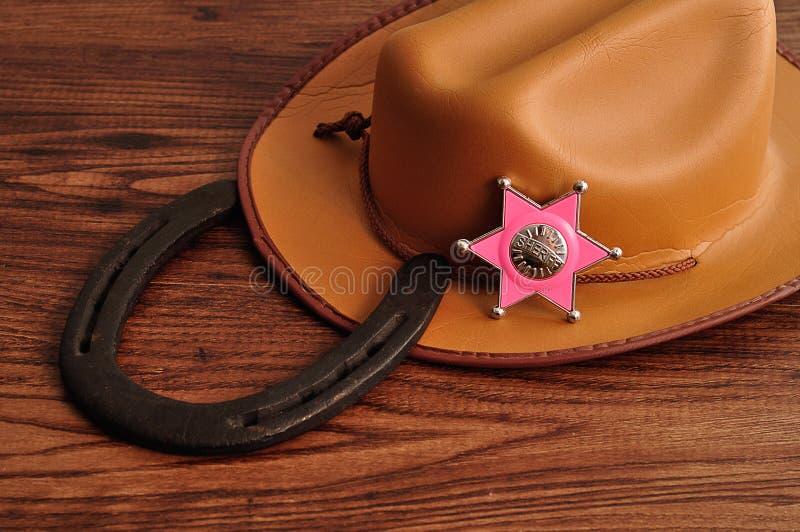 Ett sheriffemblem med en brun cowboyhatt och en hästsko royaltyfria foton