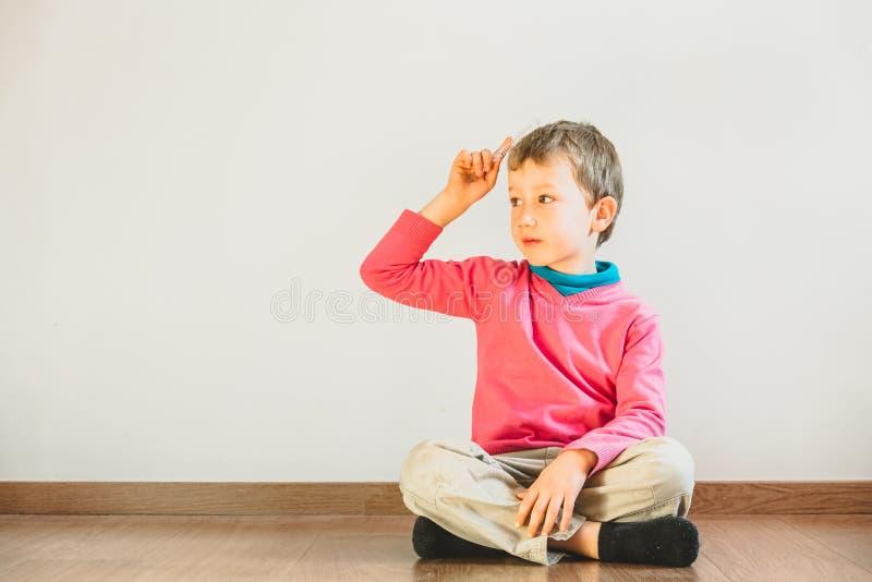 Ett självständigt barn på fem år som kämpar mot sig själv som sitter på golvet i sitt hus arkivbilder