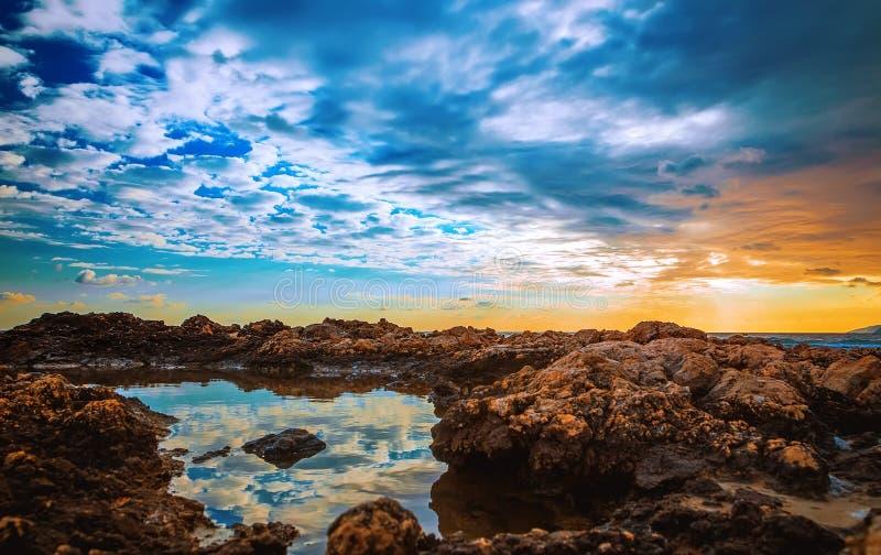 Ett sjösidalandskap på solnedgången med vita stenblock i förgrund och dramatiska moln royaltyfri bild