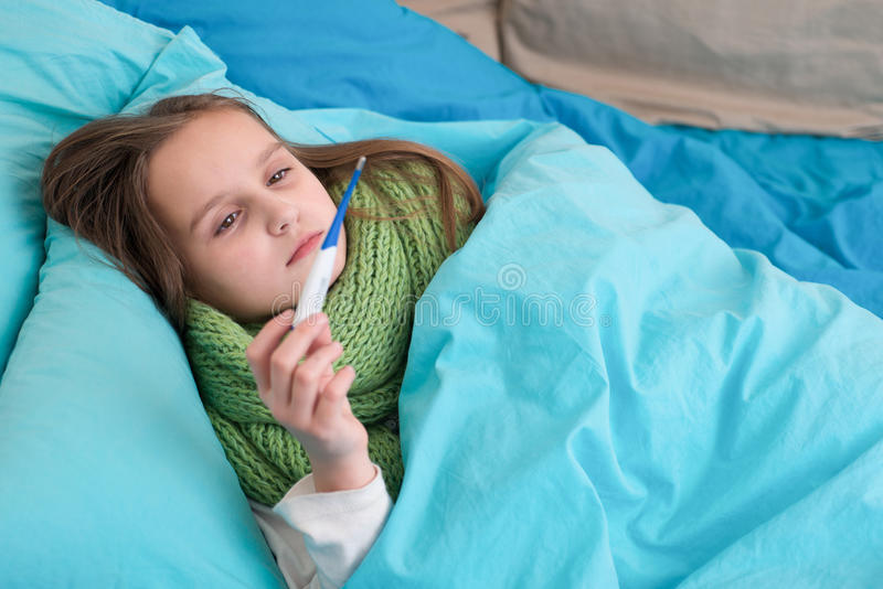 Ett sjukt behandla som ett barn att ligga i säng och att se termometern arkivbilder