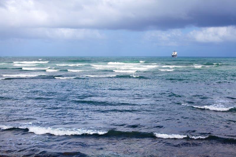 Ett skepp i avståndet skriver in havshamnen i en hamnstad, havet och vågor och en blå bakgrund för molnig himmel royaltyfria foton