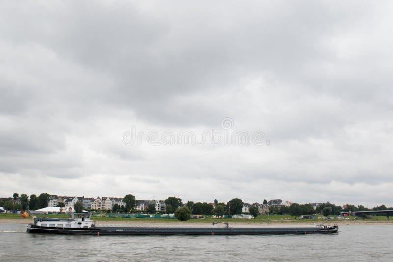 Ett skepp på dess väg över Rhinet River längs hus och den naturliga Rhenflodstranden arkivbilder