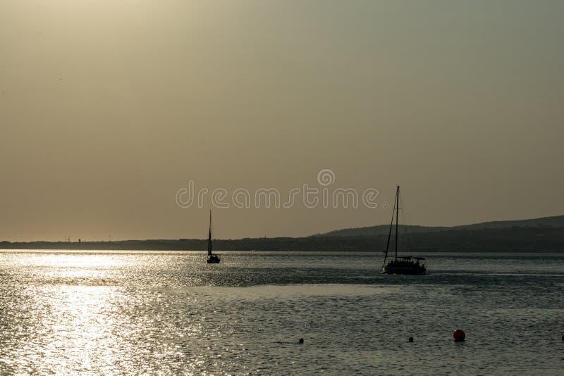 Ett skepp på en bakgrund av en silverstillhet Black Sea på solnedgången Den soliga banan på vattnet gör landskapet fridsamt arkivfoto