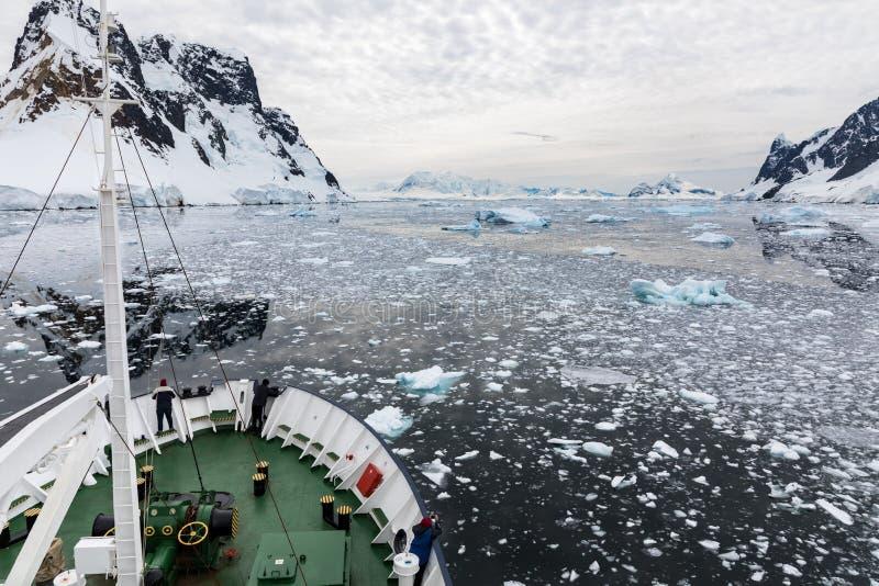 Ett skepp reser till och med snö täckte berg och vatten som fylls med is, medan passagerare ser på, den Lemaire kanalen arkivfoton