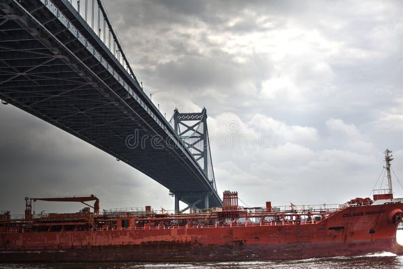 Ett skepp som går under den Ben Franklin bron royaltyfri bild