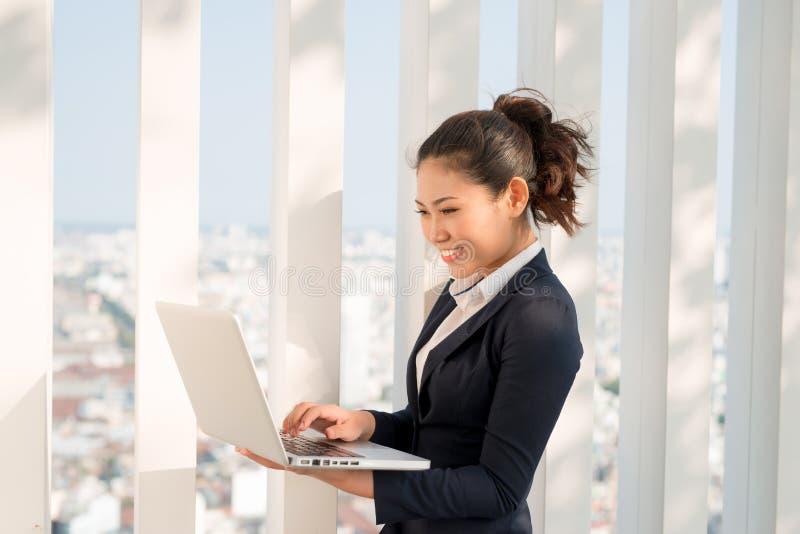 Ett skott av affärskvinnan som arbetar på hennes utomhus- bärbar dator arkivbilder