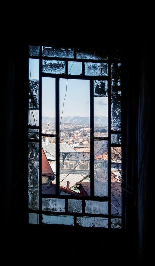 Ett slagit rökt fönster av ett gammalt hus på mitten av Tbilisi fotografering för bildbyråer