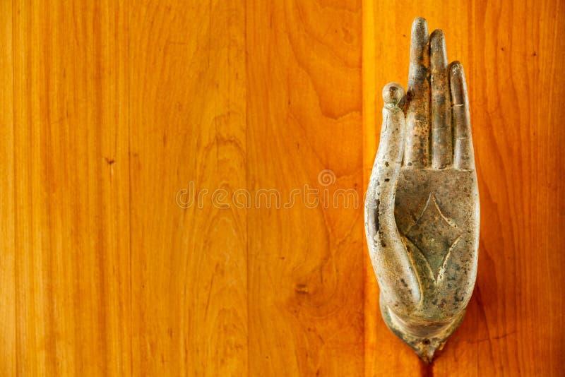Ett slut av metalldörrhandtaget i formen av bilden av Buddha` s gömma i handflatan upp royaltyfri foto
