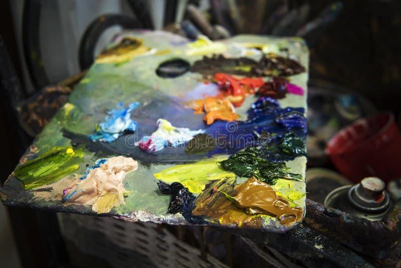 Ett slut upp av en varicoloured olje- pallette i ett målarearbetsrum En konstnärs palett som består av olika olje- målarfärger Ol royaltyfri bild