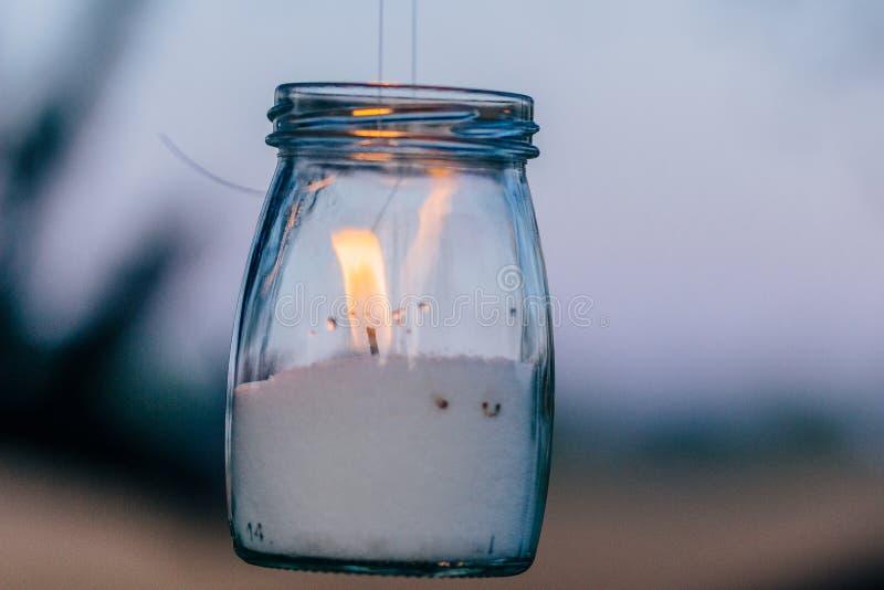 Ett slut upp av flamman från en stearinljus i murarekrus arkivfoton