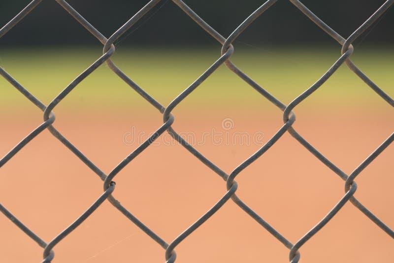 Ett slut upp av ett staket på ett baseballfält med infielden och ytterfälten som är suddiga i bakgrunden arkivbilder