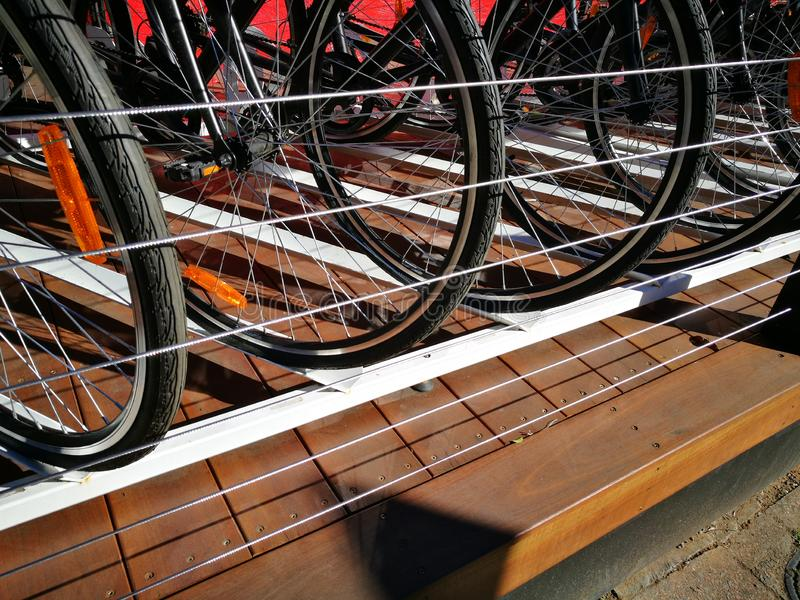 Ett slut upp propra rader av cykels hjul som parkerar på staketet royaltyfri bild