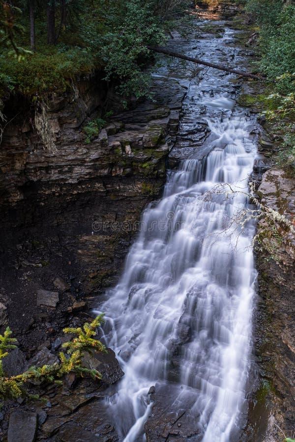 Ett slut upp sikt av en majestätisk vattenfall i provinsiella Monkman parkerar, Kanada, flödet av vattenåtstramningar till och me fotografering för bildbyråer