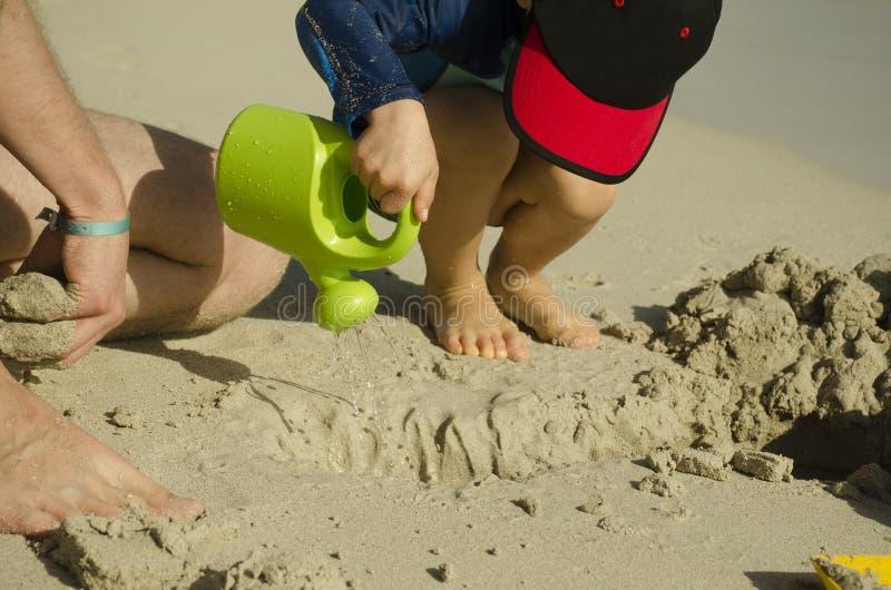 Ett småbarn i ett lock häller vatten från bevattna kan arkivfoton