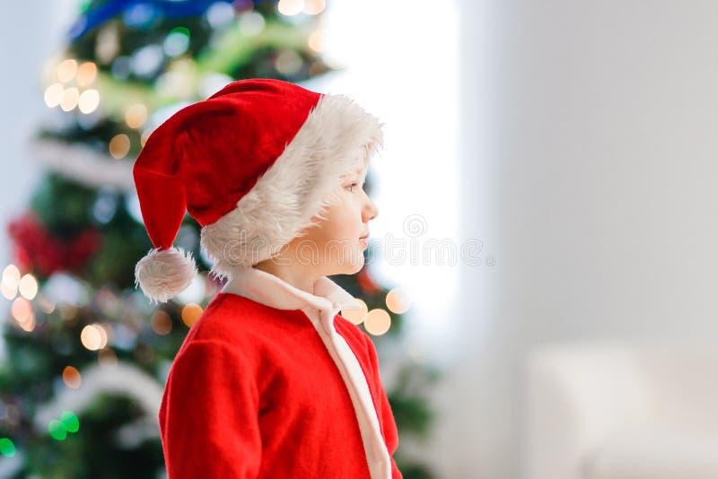 Ett småbarn i profil i jultomten passar och hatten för jul arkivbilder
