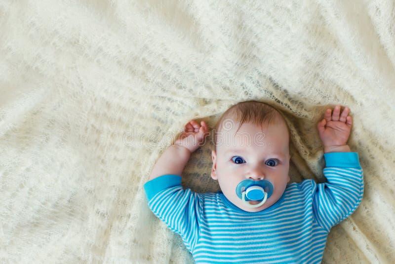 Ett småbarn ligger på en vit bakgrund i en blå skjorta royaltyfria bilder