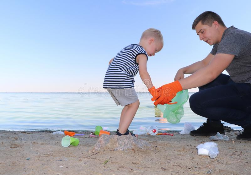 Ett småbarn samlar avfall på stranden Hans farsa pekar hans finger var att kasta avskräde Föräldrar undervisar barn renlighet royaltyfri foto