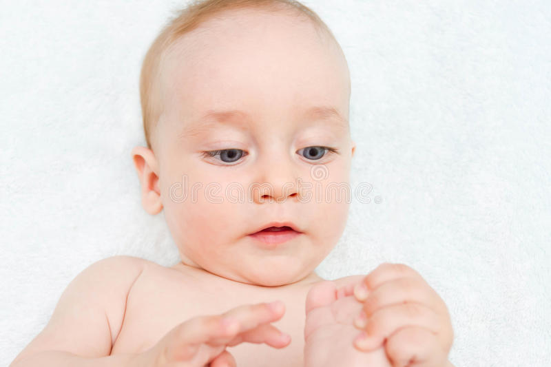 Ett småbarn ser hans fot royaltyfri bild