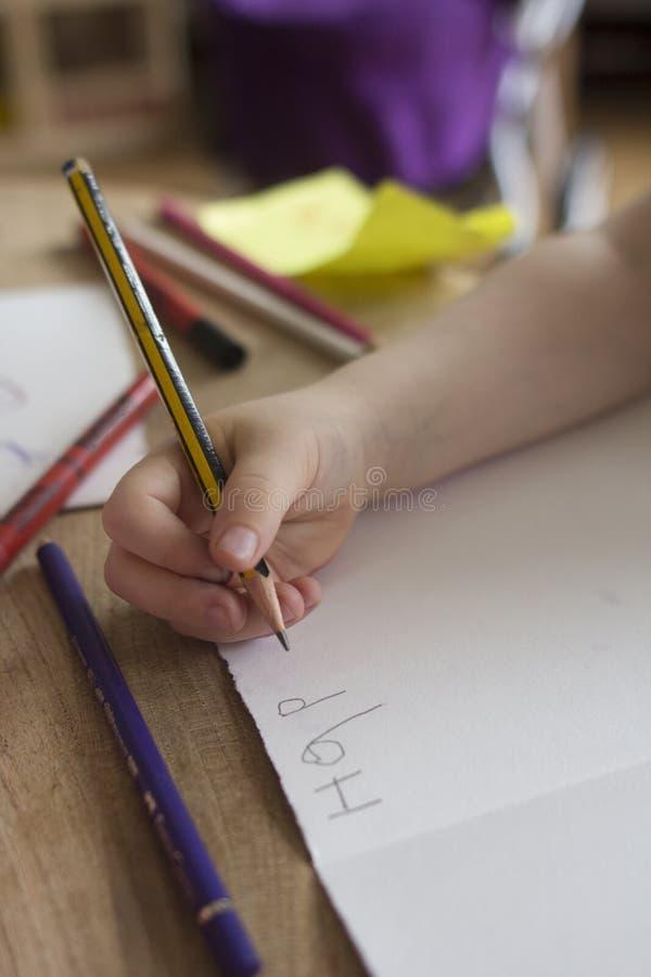 Ett småbarn skriver ut ett födelsedagkort till hennes liten tant royaltyfria foton